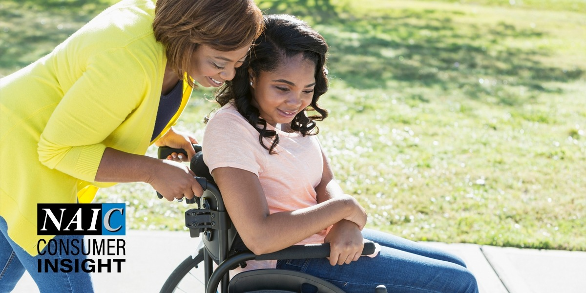 Mother pushing daughter in wheelchair